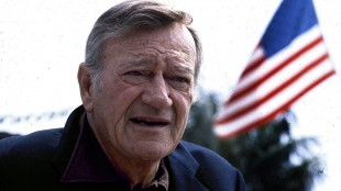 "FILE - This 1978 file photo shows actor John Wayne. Wearing a brown plaid coat worn by Wayne in 1945's ""Flame of Barbary Coast,"" Republican Lt. Gov. Dan Patrick has declared a day in honor of the quintessential screen cowboy as he presided over the Senate Tuesday, May 26, 2015. He declared it John Wayne Day in Texas to mark the Hollywood legend's 108th birthday and named the actor an honorary Texan. (AP Photo, File)"