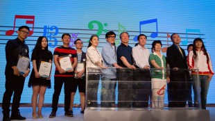 "Hong Kong movie star Jackie Chan, sixth from left, stands with Chinese officials and music composers at a launch for Olympic Music Week on stage during the 2022 Beijing's Winter Olympics bid campaign held at a hotel in Beijing, China, Wednesday, May 27, 2015. Jackie Chan is throwing his support behind Beijing's bid to host the 2022 Winter Olympics, even recording a song ""Wake Up Winter"" promoting the campaign. (AP Photo/Andy Wong)"
