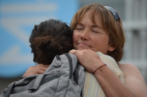 """Alysha Brilla hugs Gwen Jacob at  """"Bare with Us: Top Freedom Rally at Waterloo Town Square, Aug 1, 2015"""