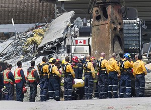 Rescue workers remove their hard hats as firefighters carry a second body out of the Algo Centre Mall in Elliot Lake, Ont., on June 27, 2012. THE CANADIAN PRESS/Nathan Denette