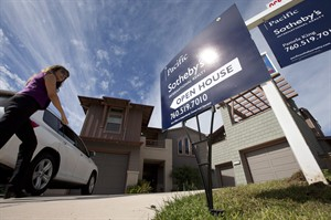 In this Nov. 14, 2012 photo, a woman walks towards a home for sale during a viewing for brokers in Leucadia, Calif. THE CANADIAN PRESS/AP, Gregory Bull