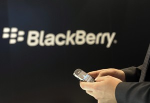 A Blackberry employee holds a Blackberry smartphone in Berlin, Nov.8, 2011. Research In Motion (TSX:RIM) beat expectations in its latest results as it reported a third-quarter profit of $9 million. THE CANADIAN PRESS/AP-Berthold Stadler