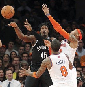 Brooklyn Nets' Gerald Wallace (45) fights for a loose ball against New York Knicks' J.R. Smith (8) and Carmelo Anthony during the first half of an NBA basketball game, Wednesday, Dec. 19, 2012, at Madison Square Garden in New York. The Knicks won 100-86. (AP Photo/Mary Altaffer)