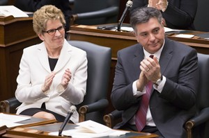 Ontario Premier Kathleen Wynne (left) and Finance Minister Charles Sousa applaud asLieutenant Governor David Onley delivers the throne speech at the Ontario Legislature in Toronto on Tuesday February 19, 2013, THE CANADIAN PRESS/Chris Young