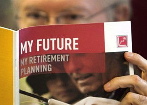 A man looks over a brochures offering various retirement savings options on February 3, 2012 in Montreal. THE CANADIAN PRESS/Ryan Remiorz