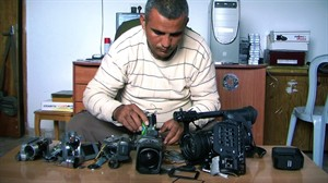 """FILE - This undated publicity photo released by Kino Lorber, Inc. shows Co-director Emad Burnat with his five broken cameras. Burnat and Guy Davidi co-directed the documentary film, """"5 Broken Cameras."""" Immigration officials briefly detained the Palestinian director of the Oscar-nominated documentary """"5 Broken Cameras"""" on his way into town for Sunday's Academy Awards. Burnat says that when he arrived at Los Angeles International Airport from Turkey with his wife and 8-year-old son late Tuesday, Feb. 19, 2013, he was told he didn't have the proper proof that he was a nominee. (AP Photo/Kino Lorber, Inc, File.)"""