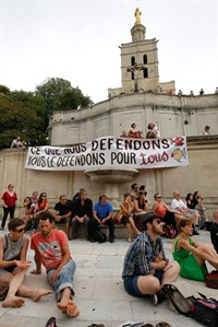 """Part-time and temporary arts workers, striking artists and theater personnel, known as 'intermittents', attend a general assembly, in Avignon, France, Friday, July 4, 2014. Organizers of one of Europe's premier theater festivals are cancelling some shows amid a protest movement by cultural workers over changes to their off-season unemployment benefits. The director of the Festival d'Avignon, Olivier Py, told journalists in Avignon that two plays scheduled for Friday's opening night have been called off. The CGT union announced a strike, but it's unclear how many workers will take part. Banner reads :""""That we defend, we defend for all"""". (AP Photo/Claude Paris)"""