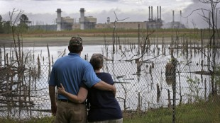 FILE - In this April 25, 2014, file photo, Bryant Gobble, left, hugs his wife, Sherry Gobble, right, as they look from their yard across an ash pond full of dead trees toward Duke Energy's Buck Steam Station in Dukeville, N.C. Duke says it will provide bottled water to residents living near coal ash pits in North Carolina. So far, more than 150 residential wells tested near Duke's dumps have failed to meet state groundwater standards. (AP Photo/Chuck Burton, File)
