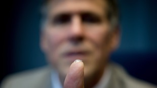 Dr. Garth Webb holds a bionic lens he developed on the tip of his finger, while sitting for a photograph at Manterra Technologies where the lens would be mass produced in Delta, B.C., on Tuesday May 12, 2015. Dr. Webb says it would allow people to see to infinity and replace the need for eyeglasses and contact lenses. THE CANADIAN PRESS/Darryl Dyck