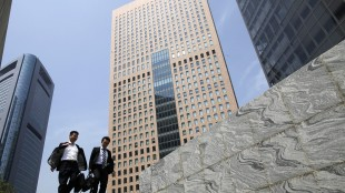 In this April 28, 2015 photo, businessmen walk by high-rise building in Tokyo. Japan has reported its economy expanded at a faster-than-expected 2.4 percent annual rate in January-March, 2015, thanks largely to a rebound in housing construction. The government reported Wednesday, May 20, 2015, that preliminary estimates show the world's third biggest economy expanded 0.6 percent from the previous quarter. It was the second straight quarter of growth following a recession in mid-2014 brought on by a sales tax hike that crippled private demand. (AP Photo/Shuji Kajiyama)