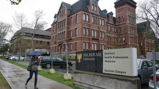A pedestrian walks by the Dalhousie Dentistry Building in Halifax on Friday, May 22, 2015. A report into sexist online posts by dentistry students at Dalhousie University has found that a Facebook page at the centre of the scandal began as a bonding exercise, but turned offensive. Despite the report's findings, the university says the academic standards class committee determined the men are eligible to graduate as long as they satisfy their clinical requirements. THE CANADIAN PRESS/Darren Pittman