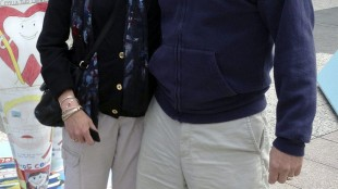 In this July 2014 photo provided by Karen Friend, Friend, left, stands with her husband, Jacob Vinton, on Michigan Avenue in Chicago. Friend, a professor at Brown University in Providence, R.I., took four weeks off in 2014 after her 59-year-old husband, who has early-onset Alzheimer's disease, was hospitalized with tremors. She used the time to make sure he was medically stable and hire help. (Courtesy of Karen Friend via AP)