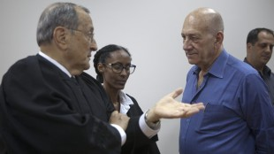 Former Israeli Prime Minister Ehud Olmert, right, listens to his defense team, at the Jerusalem District Court, Monday, May 25, 2015. Olmert was sentenced Monday to eight months in prison for unlawfully accepting money from a U.S. supporter, capping the dramatic downfall of a man who only years earlier led the country and hoped to bring about a historic peace agreement with the Palestinians. (Heidi Levine/Pool Photo via AP)