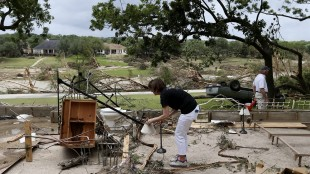 Debi Welsh, of Corpus Christi, Texas, picks up a lamp while helping clean up the remains of her family home that washed away, Monday, May 25, 2015, in Wimberley, Texas. Around a dozen people were reported missing in flash flooding from a line of storms that stretched from the Gulf of Mexico to the Great Lakes. (Jerry Lara/The San Antonio Express-News via AP)