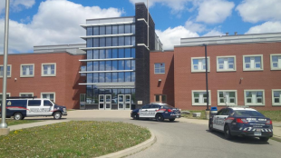Police vehicles sit outside Huron Heights Secondary School after Hold and Secure situation Friday May 23, 2015.