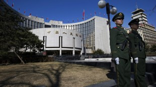 FILE - In this Wednesday, March 13, 2013 file photo, Chinese paramilitary policemen stand on duty outside the People's Bank of China in Beijing, China. China's central bank said Sunday, May 10, 2015, that it is cutting interest rates for the third time in six months to boost the country's sluggish economy. (AP Photo/Ng Han Guan, File)